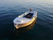 Boat on calm sea. Wooden boat anchored on dark calm sea Royalty Free Stock Photos