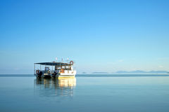 A boat on calm sea at Kota Kinabalu, Malaysia. A boat on a calm sea and lands on the background. Beautiful clear blue sky and nice blue color reflection on the Stock Images