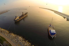 Boat in calm sea at sunset. Aerial Shot. Fisher boat and a cargo ship berthed against sunset in calm sea Royalty Free Stock Photos