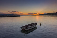 Boat in calm water at sunset Stock Image