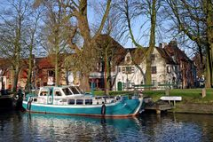 Boat on a canal in Bruges. With old houses in background Stock Photo