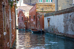Boat on canal among houses. Venice, Italy. Royalty Free Stock Images