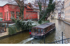 Boat on the canal in Prague on a day near the house and a cafe on the waterfront in winter day. Czech Republic Stock Photography