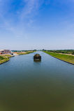 Boat in  canal. A boat in a canal on a sunny day Royalty Free Stock Images