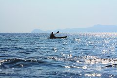 Boat and canoe on the blue sea Royalty Free Stock Image