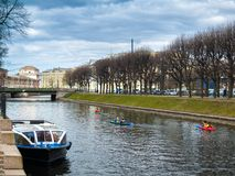 Boat and boat canoes on the Moika River in the early spring in A. River Moika and a boat with canoe boats floating along the river in the center of the city of Stock Image