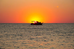 A boat carries the sun at the sunset Stock Photography