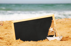 Boat and chalkboard, on sea sand and ocean horizon Royalty Free Stock Photography