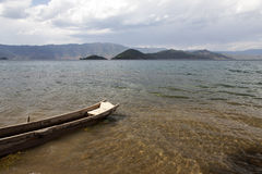 Boat on Clear Lake. A small wooden boat rests on the shore of Lugu Lake in Yunnan province, China Royalty Free Stock Photo