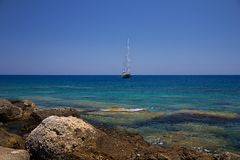 Boat. Clear sea and sailboat moored near the rocky coast Royalty Free Stock Photography