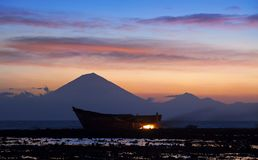 Boat on coast of Gili Trawangan island in Indonesia. A silhouette of a boat on the coast of the Indonesian island Gili Trawangan at dusk with mountains in the stock photo