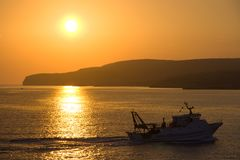Boat And Coastline At Sunset, Malta. Boat and Coastline of Gozo, Malta at sunset Royalty Free Stock Image