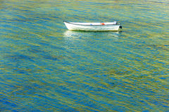 Boat on colorful blue and green water Royalty Free Stock Image