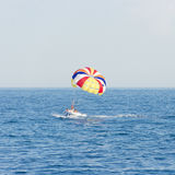 Boat with colorful parachute floating in sea. Boat with the colorful parachute floating in the sea Royalty Free Stock Photo