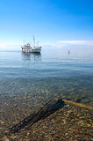 Boat coming to shore in clear water (lake Baikal). Ship comes to shore on pebble lake with clean water and bottom of lake is visible Stock Photos