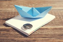 Boat and compass on notepad on wooden background royalty free stock images