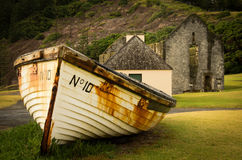 Boat and Convict Ruins, Norfolk Island. An old lighter (small boat) in front of ruins from the convict settlement on Norfolk Island royalty free stock photo