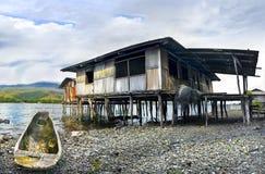 Boat and cottage on piles ashore lake sentani stock photos
