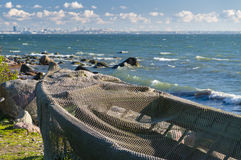Boat covered by fisherman net at seashore and modern cityscape Stock Photos