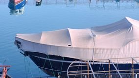 Boat covered with tarpaulin in the seaport is parked on the water. stock video