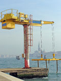 Boat crane, Venice. Yellow boat crane on the Giudecca embankment, Isola di San Giorgio Maggiore background Stock Photo