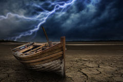 Boat crash land to the ground dry and cracked. With lightning st Royalty Free Stock Images
