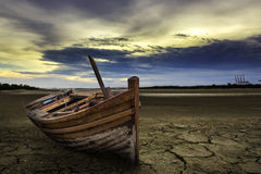 Boat crash landing land with dry and cracked ground. Desert Stock Images