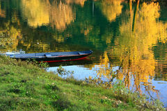 Boat at Crnojevica river with colorful trees reflection, Montene Stock Photos