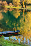 Boat at Crnojevica river with colorful trees reflection, Montene Royalty Free Stock Photos
