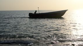 Boat crossing calm water surface of ocean during golden evening sundown on horizon, beautiful scenery of tranquil. Seascape in summer evening twilights stock video footage