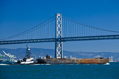 Boat crossing under Oakland bridge Stock Photography