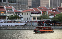 Boat Cruise. Singapore - June 2016 A boat cruising down Singapore River passing the old shophouses along Boat Quay royalty free stock photos