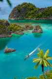 Boat Cruising Around small green Islands belonging. To Fam Island in the sea of Raja Ampat, Papua New Guinea, Indonesia Royalty Free Stock Photos