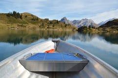 Boat cruising a mountain lake Stock Images