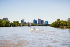 Boat cruising on the muddy looking water of Sacramento river; the City`s downtown skyline in the background; California royalty free stock images