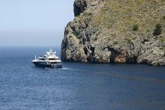 Boat cruising by sea cliffs royalty free stock image