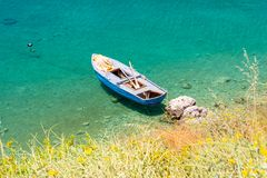 Boat on crystal clear water of ionian sea in Porto Palermo in Albania stock photo