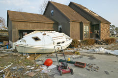 Boat and debris in front of house Royalty Free Stock Images