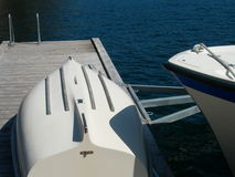 Boat Dock. Showing the front point of a docked boat, and another boat laying upside down on the pier Stock Photography