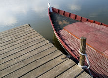 Boat and Dock. Old red fishing boat tied to a wooden dock in a lake Royalty Free Stock Photo