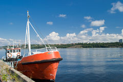 Boat at dock. A red boat docked on a beautiful summer day Stock Photos