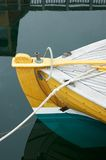 Boat at Dock. Detail of a wooden boat, tied to a dock with reflections in the water below it Royalty Free Stock Images