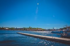 View of the pier for ships and ships in Helsinki, Finland, with the reflection of the sun on the water on a sunny day against a cl royalty free stock photography