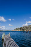 Boat dock and cliffs in the background. Boat dock also used as bath bridge, landscape with cliffs and blue sky Royalty Free Stock Photo