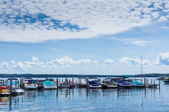 Boat dock on an New England lake on bright cloudy blue day. Beautiful new England lake on bright cloudy blue day royalty free stock images