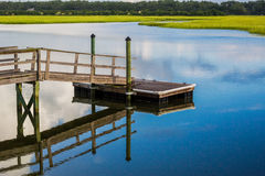 Boat Dock reflecting in inlet marsh water Royalty Free Stock Photos