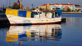 Boat in dock. Ship is anchored at harbor and mirrored on peaceful gulf water in Williemstad,  Curacao Stock Images