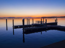 Boat dock at sunset. On a tranquil lake Royalty Free Stock Photography