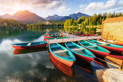 Boat on the dock surrounded by mountains at sunset. Stock Photography