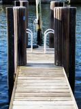 Wooden Boat dock with water view backgound. Boat dock with water view and two silver walk up handles Stock Photo